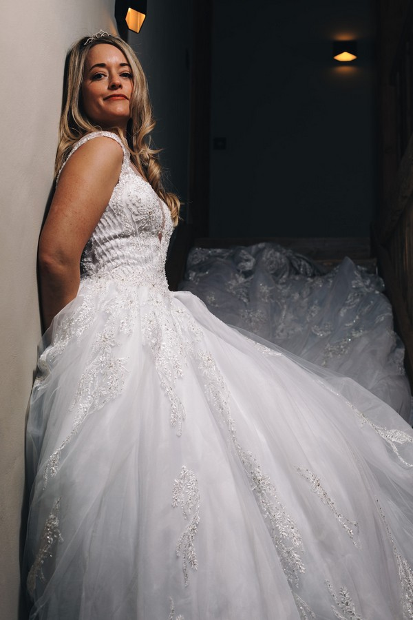 bride leans against wall and smiles down to camera standing in a stairwell