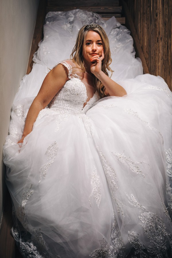 bride sits in stair well surrounded by her voluminous wedding skirt