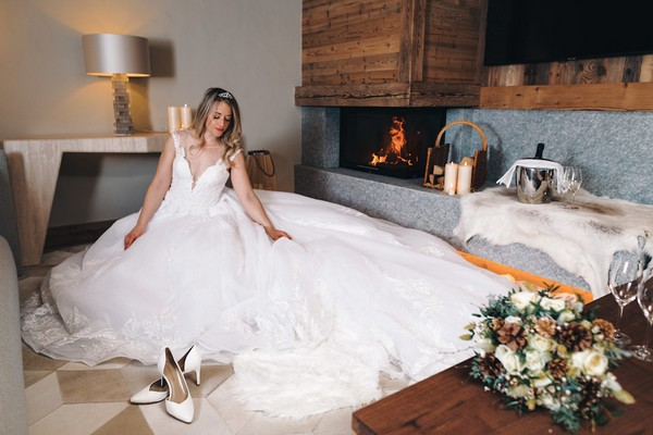 bride sits in her voluminous wedding dress on the floor in front of a fire in a private chalet in Saint-Nicolas de Véroce