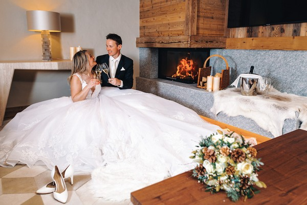 bride and groom cheers champagne in front of a fire in a private chalet in Saint-Nicolas de Véroce