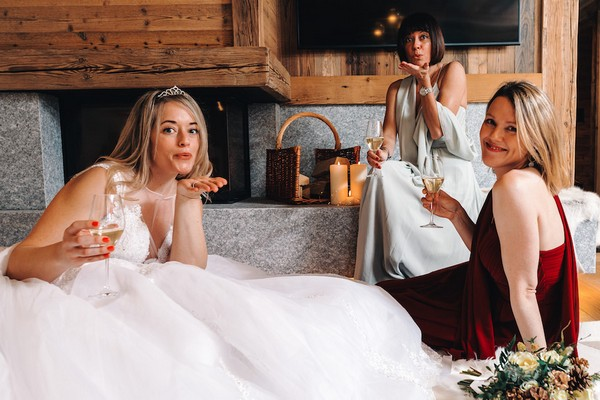 bride blows a kiss to the camera holding a glass of champagne with her bridesmaids who are wearing red and pale green