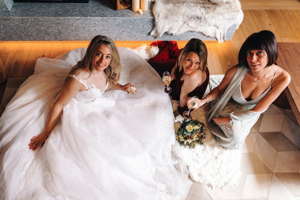 bride and bridesmaids sit on the floor and are photographed from above they are smiling up at the camera