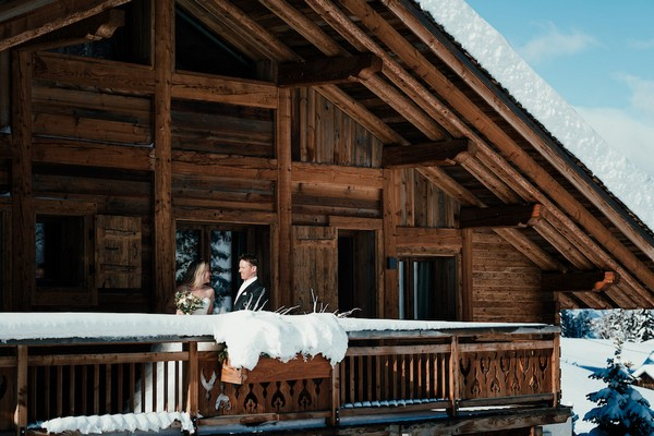 Bride and groom on the balcony of a wooden private chalet for their magical alpine village wedding in the French Alps