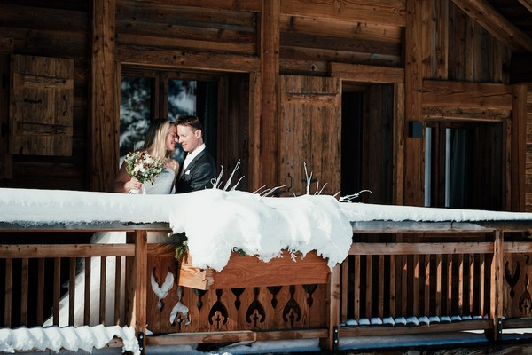 bride and groom smile on the wooden balcony of a snow covered private chalet in the French Alps