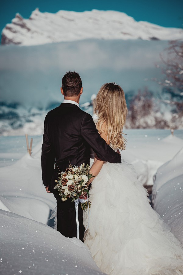 bride and groom have backs turned to camera and are completely surrounded by sparkling snow and french snowy alps