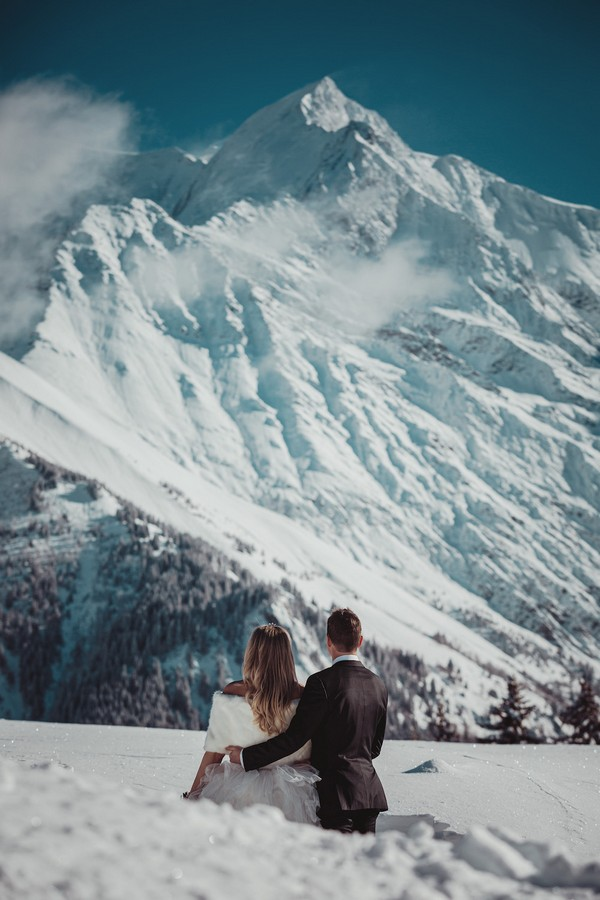 large snow covered mountain makes up the majority of this photo of a bride and groom arm and arm in the snow