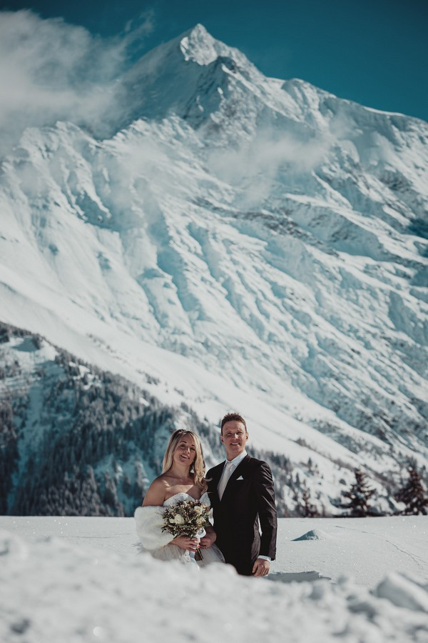 bride and groom smile in front of stunning scenery of snow covered french alps
