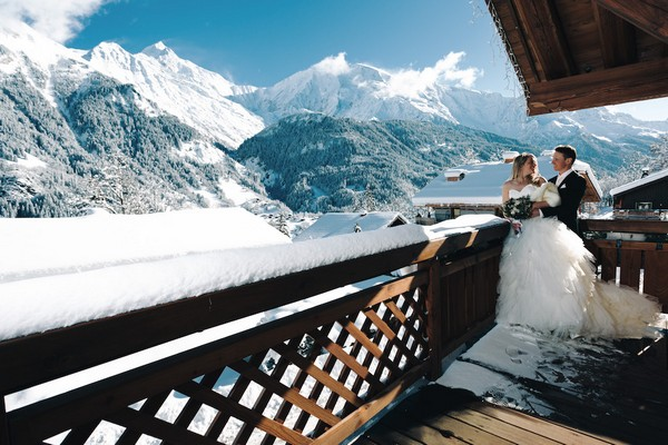 bride and groom on snowy balcony of french alps private chalet