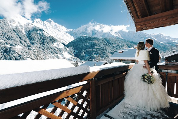 bride wears white fur wrap and groom wears black suit on the snowy balcony of a French chalet overlooking snow covered mountains