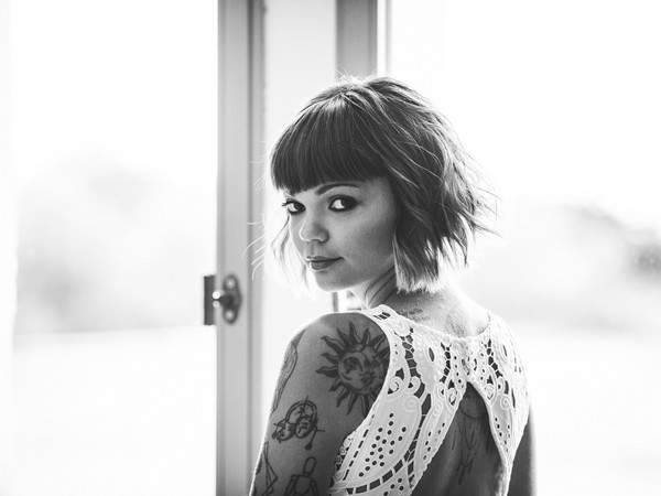 tattooed bride with short bobbed hair looking back at camera in boho style dress