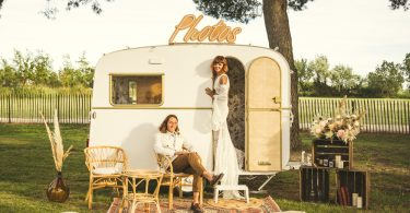 """Ema & Hyppolite In """"A Boho Wedding In Camargue"""" Feature Image of bride and groom in small campervan that has been set up as a photobooth"""
