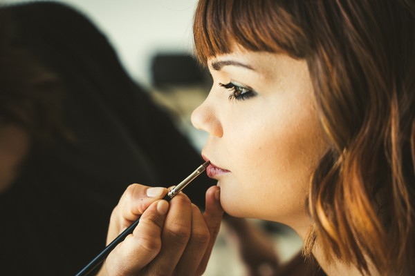 short-haired bride having burgundy lipstick applied by make up artist