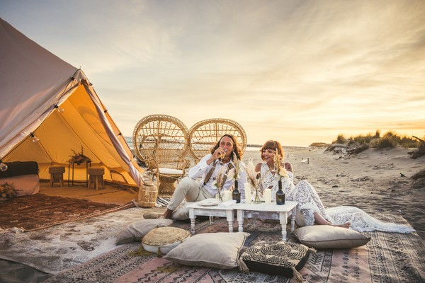 tent and carpets set up on a beach in Camargue for boho wedding of Ema and Hyppolite where they sit and drink wine