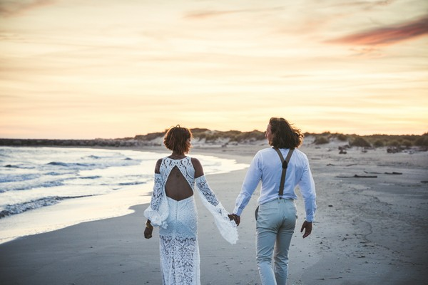 Couple walk hand in hand with back to camera on beach at sunset