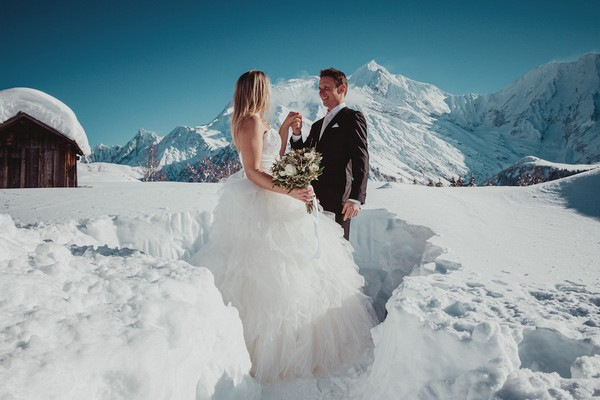 groom takes his brides hand waist high in the white snow with the french alps in the background