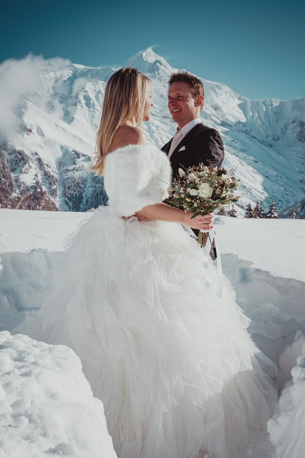 bride in white fur wrap smiles at her groom with snowy mountain in the background. they are standing waist high in white snow