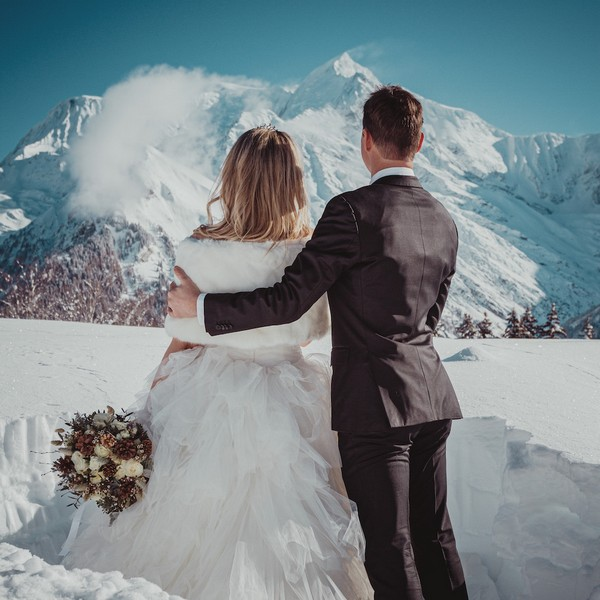 groom has his arm around his bride as they look up at the snowy mountains in the distance.