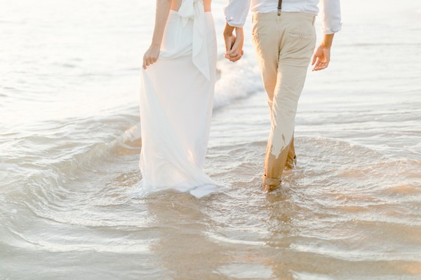 Bride and groom's feet in water of beach shore wearing all white